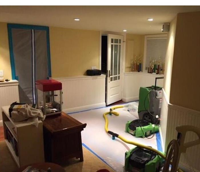Room with the flooring taped off, with SERVPRO equipment on the floor. Room also has furniture moved to one side of the home