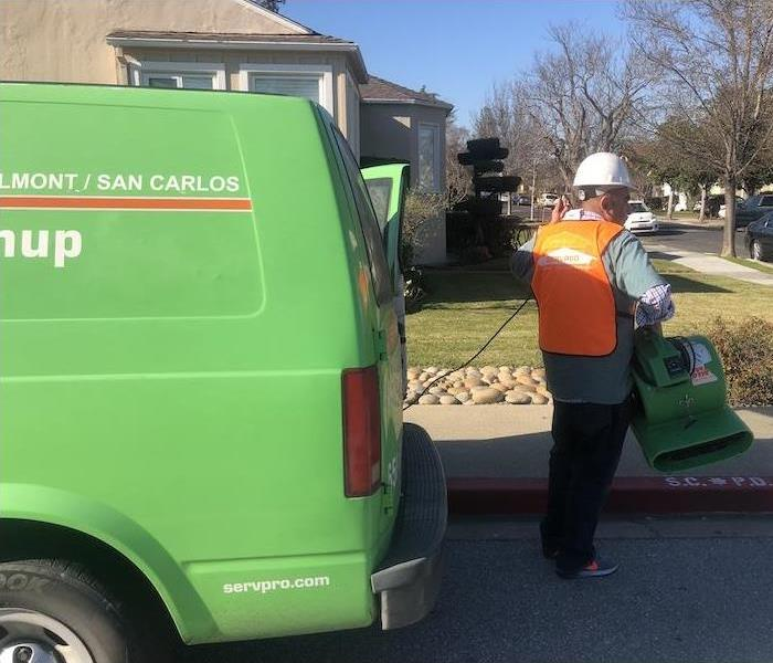 SERVPRO technician getting equipment out of the service vehicle.