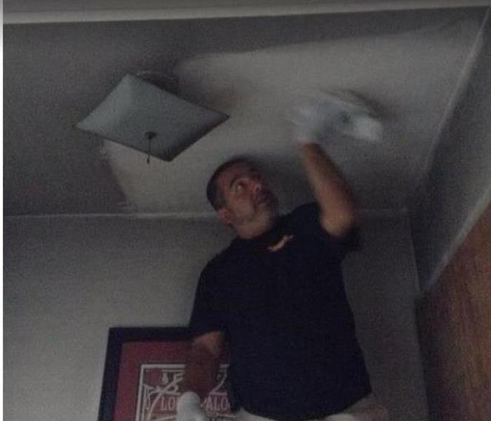 SERVPRO tech wiping soot from ceiling of fire damaged room